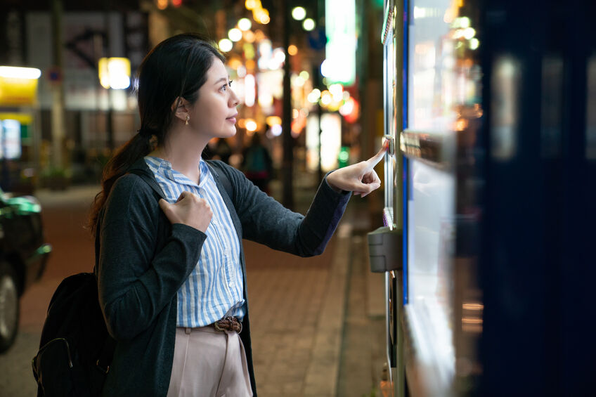 Woman standing at a vending machine looking at the options
